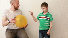 Father and son. Fearlessness lesson. Adult man suddenly poking a balloon, lit Stock Footage
