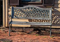 isolated wood and iron bench on wood old far west style house background - stock photo