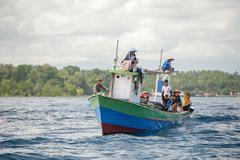BUNAKEN, INDONESIA - APRIL, 5 2014 - fishing ship returning to fisherman vill - stock photo