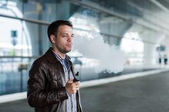 Man with a bristle smoking e-cigarette vaporizer box mode outdoors near the - stock photo