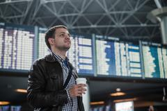 Young man with a bag in airport near flight timetable holding cup of coffee - stock photo