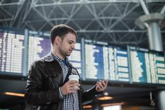 Cheerful man with coffee on the mobile phone in front of Board schedules in Stock Photos
