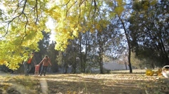 Beautiful young family walks in the park, mother father and baby daughter Stock Footage
