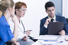 Three experienced doctor in hospital thinking about the case. Planning patient's - stock photo