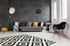 Modern living room with big space in the middle. By the wall comfortable grey co - stock photo