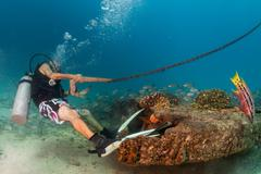 Boat chain anchor from underwater helded by diver Stock Photos