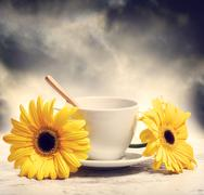 Coffee cup with yellow gerberas Stock Photos