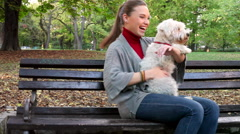 Young woman hugging her white dog in the park outdoor - stock footage