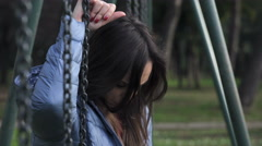 Sad, pensive young woman sit on a swing in a deserted park Stock Footage