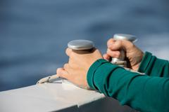 Children hands while holding boat bollard on blue sea background Stock Photos
