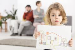 Upset little boy holding a drawing of a house, with his parents sitting angry on Stock Photos