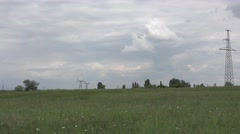 Electrical Power pole with wires in a meadow, metal structures Stock Footage