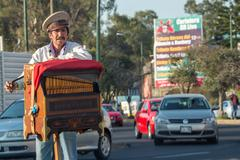 MEXICO CITY, MEXICO - FEBRUARY, 9  2015 - Poor man playing hand organ on the  - stock photo