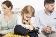 a gloomy young family with a sad little bou hugging a teddy bear, and his parent - stock photo