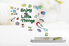 Enjoy The Little Things concept with smartphone on white table Stock Photos