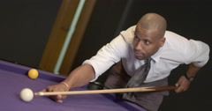 African American business man takes shot on purple pool table 4K Stock Footage