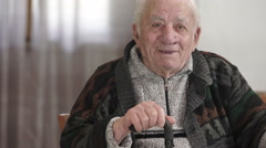 Smiling grandfather on armchair with his stick Stock Footage