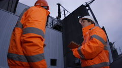 4K Male & female engineers at power station, looking at computer tablet Stock Footage