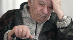 worried pensioner takes his head with hand and keeps other hand on his stick - stock footage