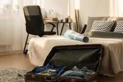 Man's bedroom arranged in natural style, filled with items connected with travel - stock photo