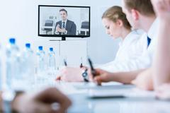 Young handsome businessman giving advice during video conference online with man - stock photo