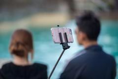 Selfie using remote control and extension tripod - stock photo