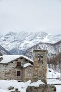 mountain stone church bell tower detail on snow background - stock photo