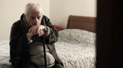 Sick old man sitting on the bed in the nursing home Stock Footage