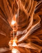 Antelope Canyon view with light rays on sand floor Stock Photos