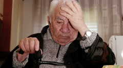 Pensive grandfather rested to his chin, thinking holding his headwith a hand Stock Footage