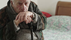 Thoughtful, sad elderly man with chin on his cane - stock footage