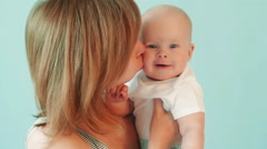 Beautiful woman kisses her son on the cheek on a blue background. - stock footage