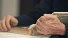 Detail of grandfather's hands leafing photo album - stock footage