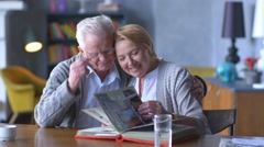 Elderly happy couple looking old photo album and smiling Stock Footage