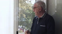 Profile of elderly man while smoking at the window Stock Footage