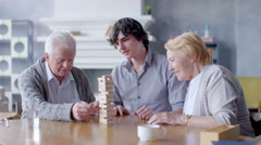 happy senior man and woman playing Board game with his grandson - stock footage