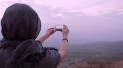 Muslim woman taking photo with smartphone Stock Footage