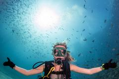 beautiful diver blonde girl diving in the deep blue sea - stock photo