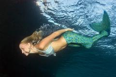 Blonde beautiful Siren Mermaid while diving underwater in the deep blue sea Kuvituskuvat