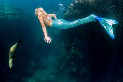 Blonde beautiful Siren Mermaid while diving underwater in the deep blue sea Kuvituskuvat