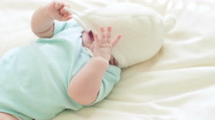 Child in a fluffy hat plays in bed. - stock footage