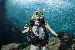 beautiful diver blonde girl diving in the deep blue sea  Inside a school of f - stock photo