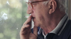 Old man with glasses smokes at the window Stock Footage
