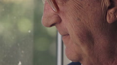 Focus on pensioner while smokes at the window - stock footage