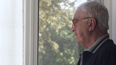 Loneliness: old man alone looks sadly out the window Stock Footage