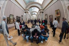 PARIS, FRANCE - APRIL 30, 2016 - Louvre museum crowded of tourist taking pict Stock Photos