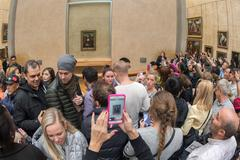 PARIS, FRANCE - APRIL 30, 2016 - lot of people inside louvre museum, taking p Kuvituskuvat