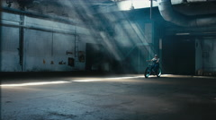 Young male in denim overalls riding his custom bicycle in large warehouse garage Stock Footage