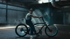 Young Caucasian male in denim overalls riding custom bicycle in warehouse garage - stock footage