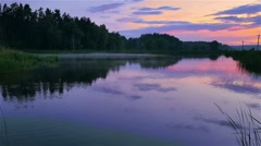 Fog creeps over the beautiful lake at amazing sunset near the forest - stock footage